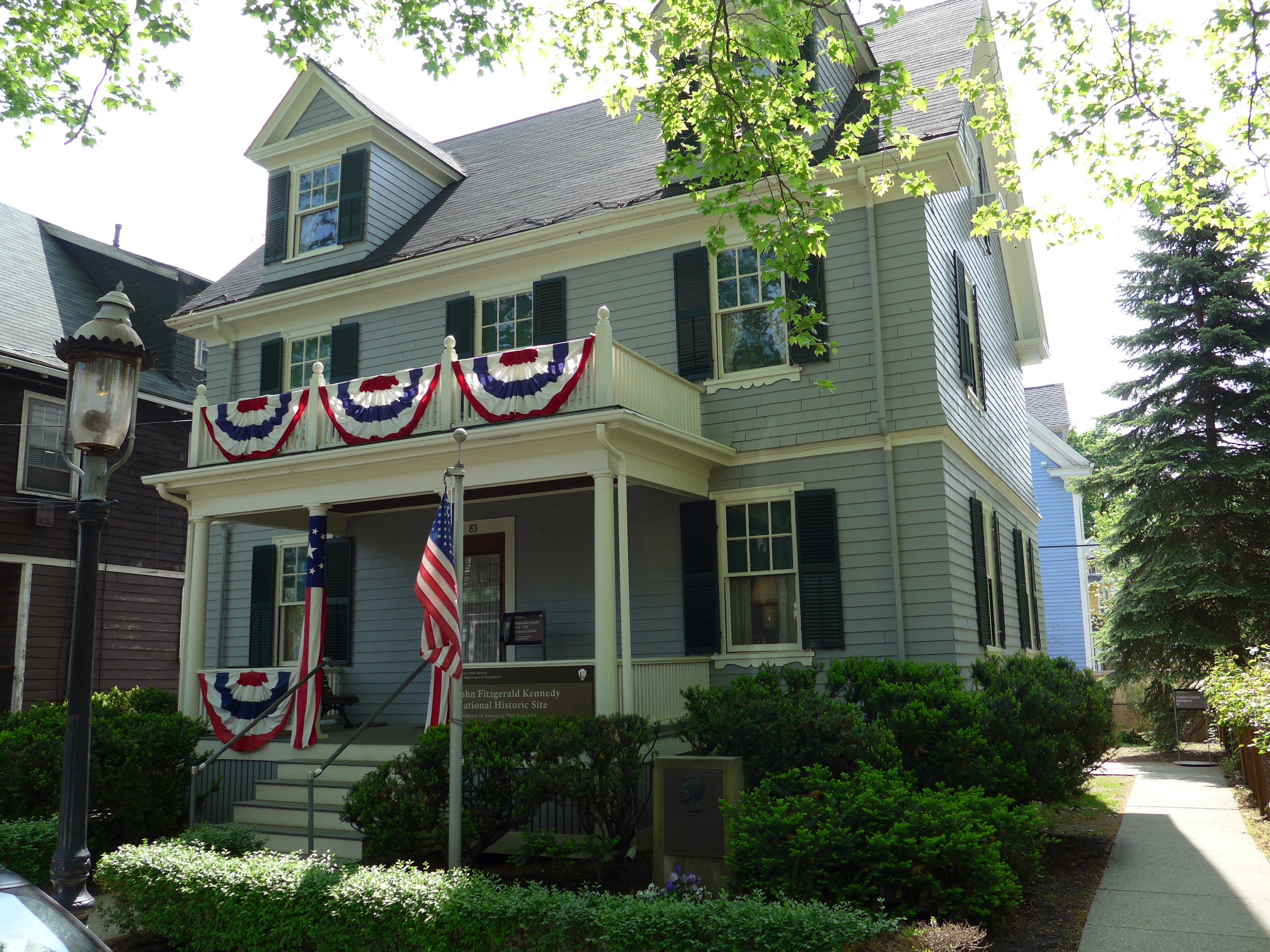 The front of the two-story house with red, white, and blue half-circle flags adorning the banisters at John F. Kennedy National Historic Site