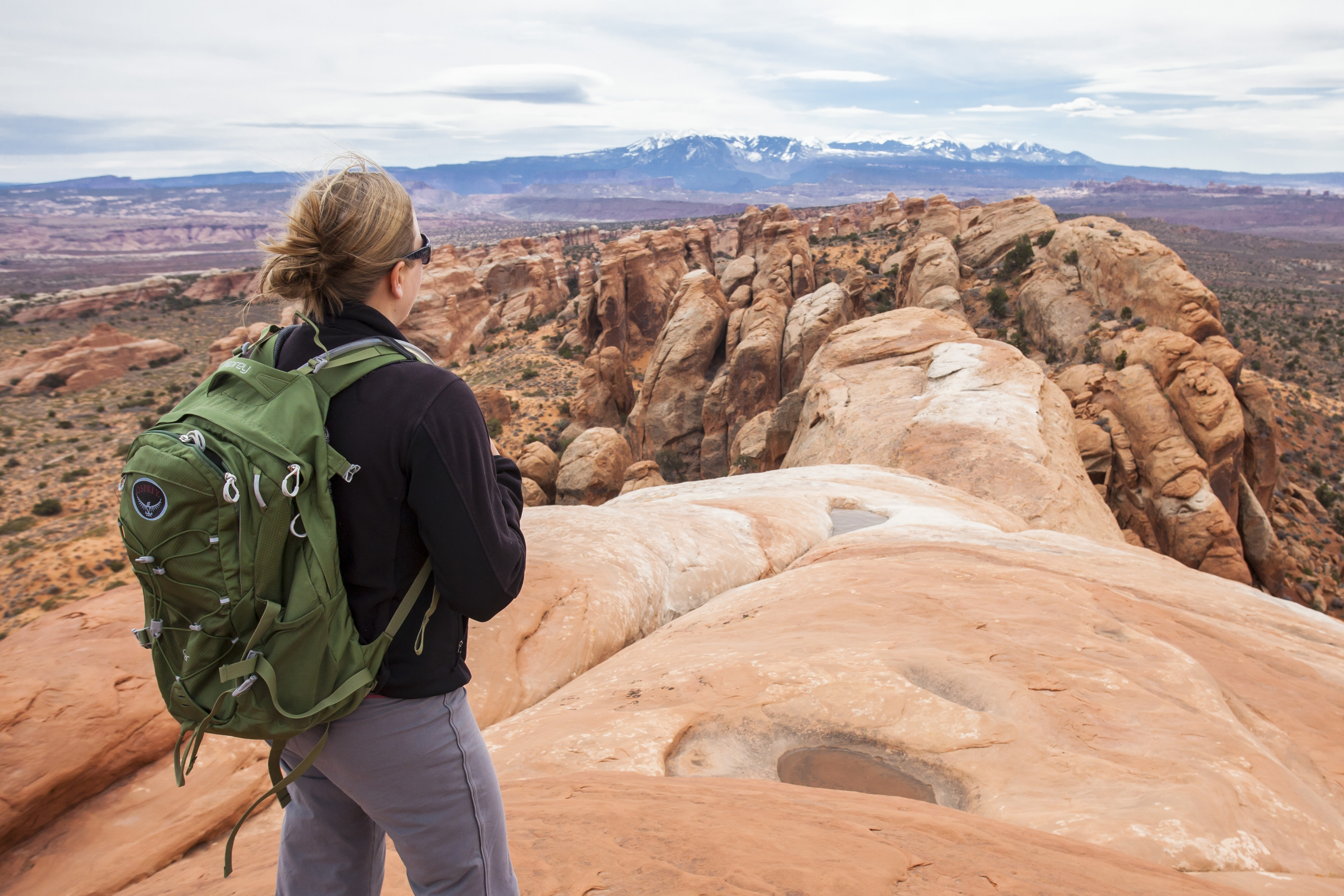 A hiker looks over the expanse at Arches National Park.