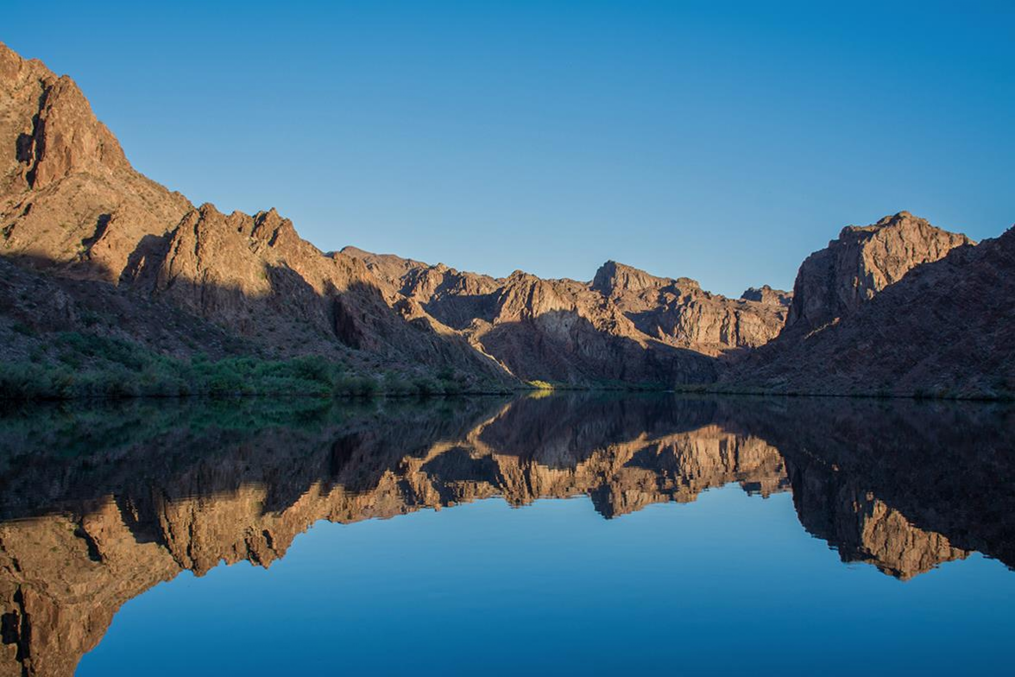 The red sandstone canyon walls reflecting in the still waters of the Black Canyon Water Trail at Lake Mead National Recreation Area