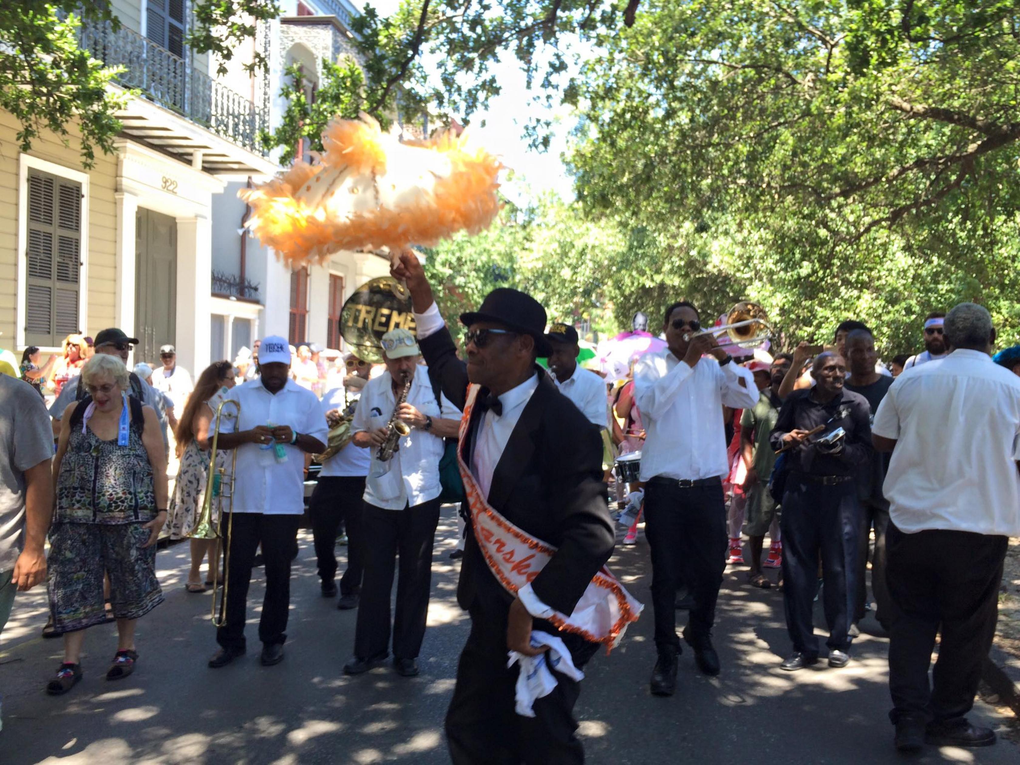 Un grupo de personas bailando jazz a la sombra en las calles del Parque Histórico Nacional de Jazz de Nueva Orleans