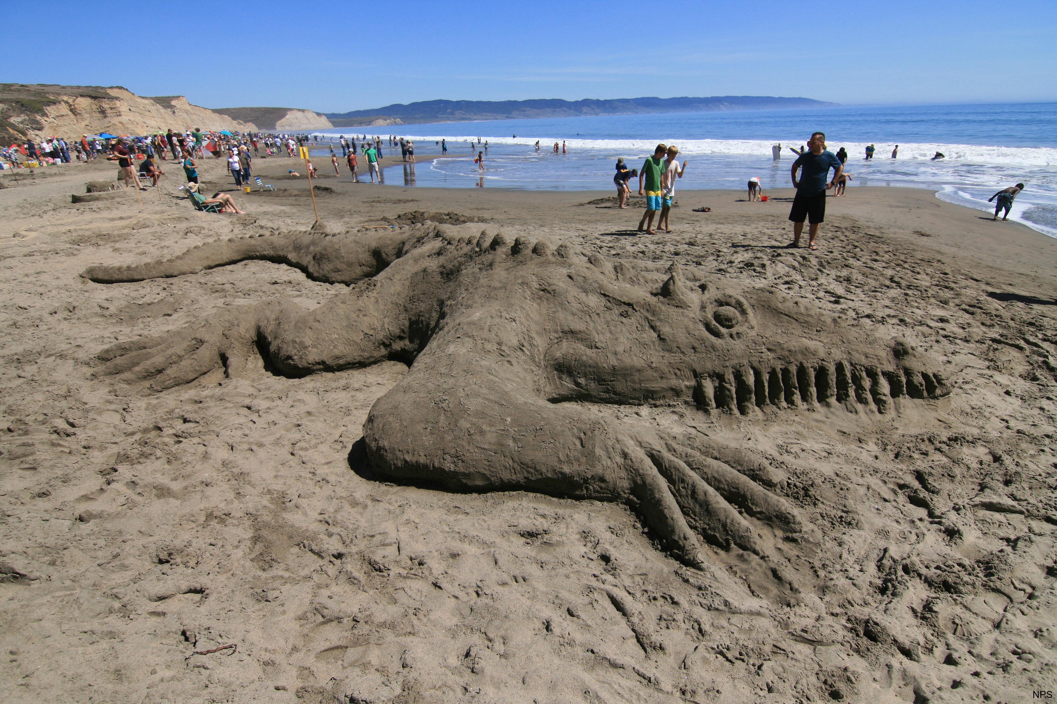 Un concurso de castillos de arena produce un dinosaurio en una playa llena de gente en Point Reyes.