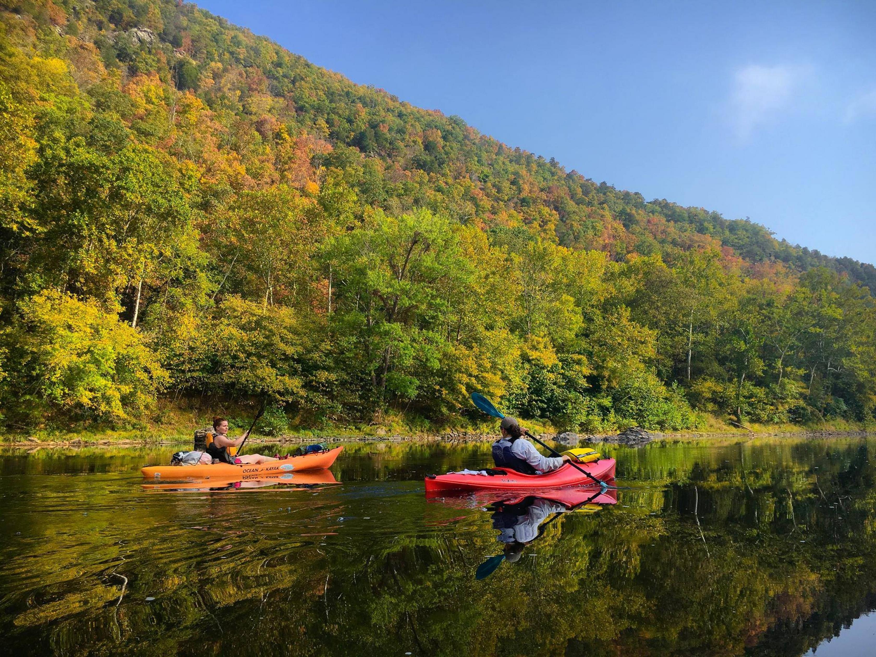 Dos kayakistas remando por el río Potomac bordeado de árboles de otoño a lo largo del sendero escénico nacional Potomac Heritage