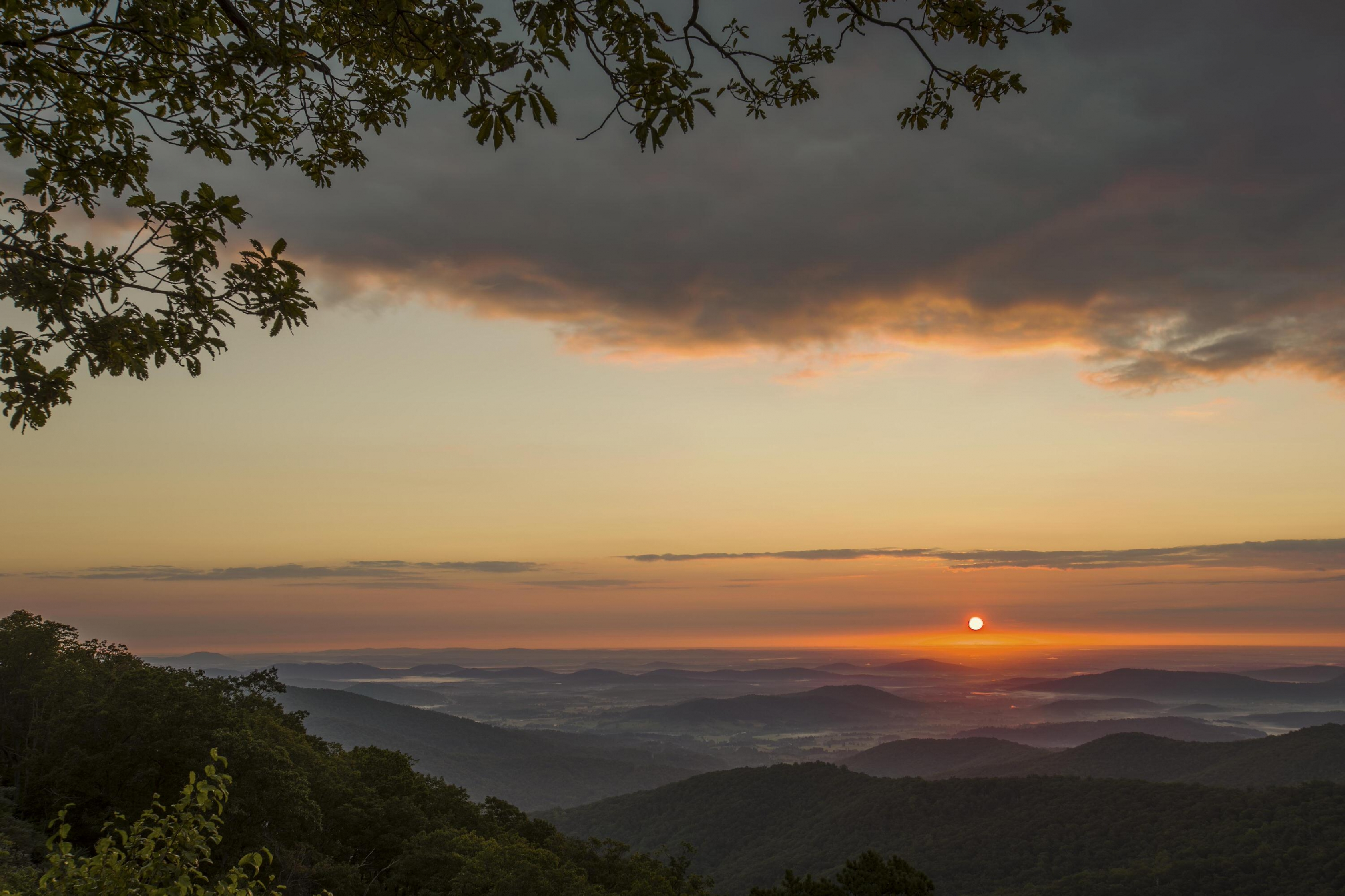 Orange sun rising over the misty valley from Hazel Mountain Overlook at Shenandoah National Park