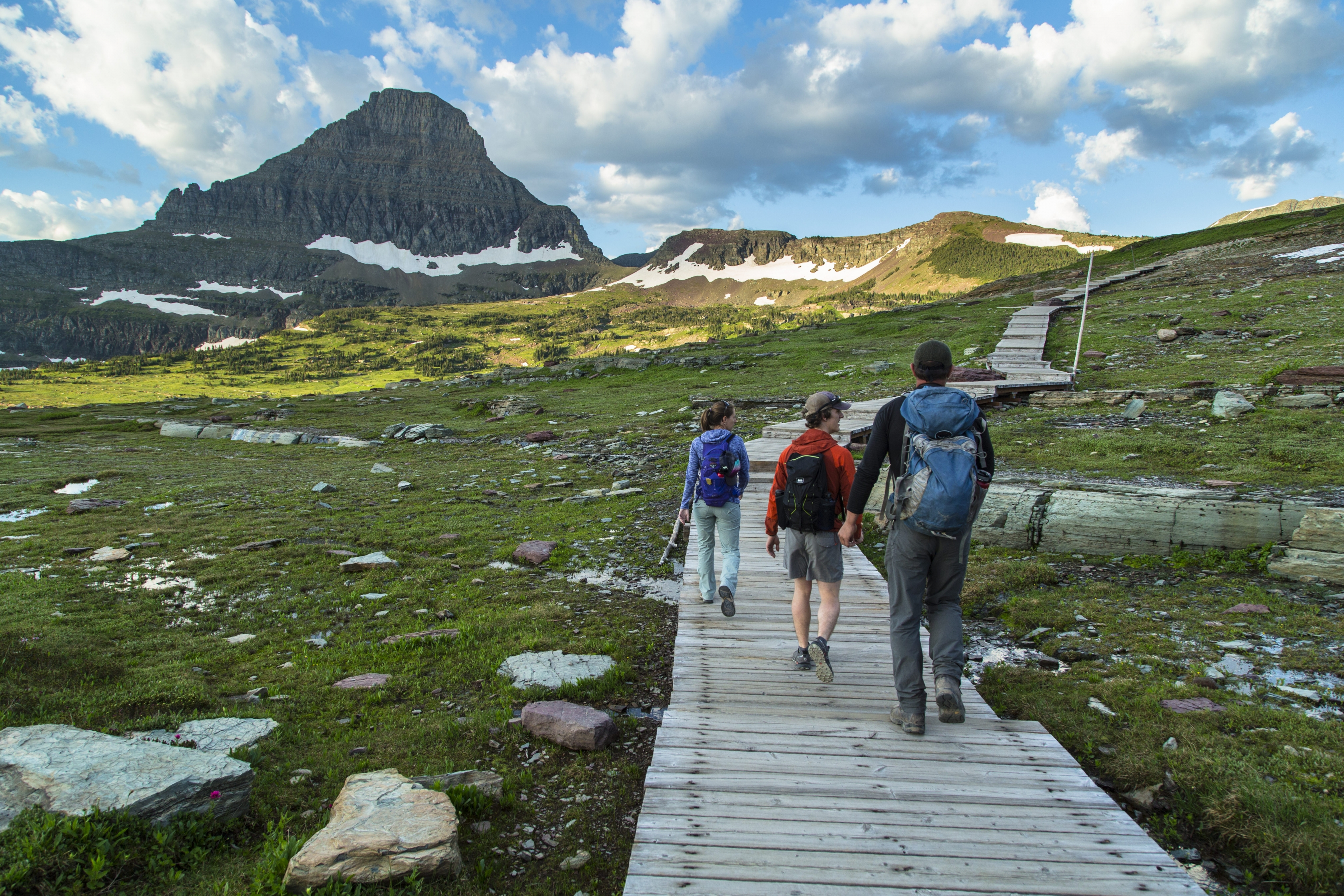 A group of three hikers in Glacier National Park.