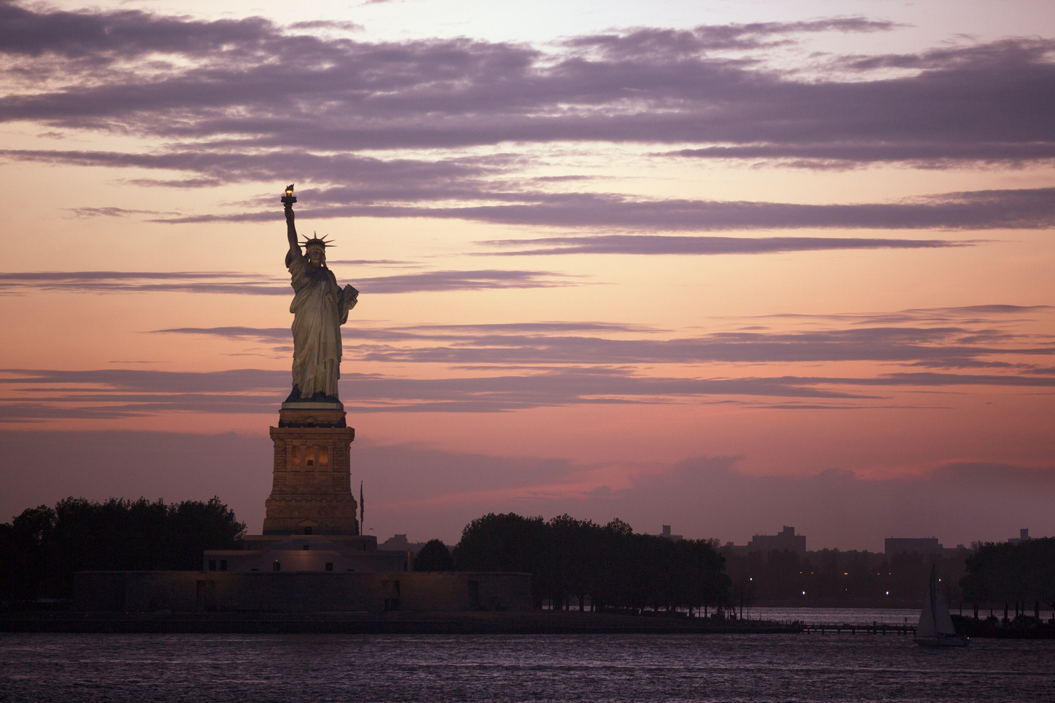 colorful red and orange sunset with purple clouds behind a dimly lit Statue of Liberty