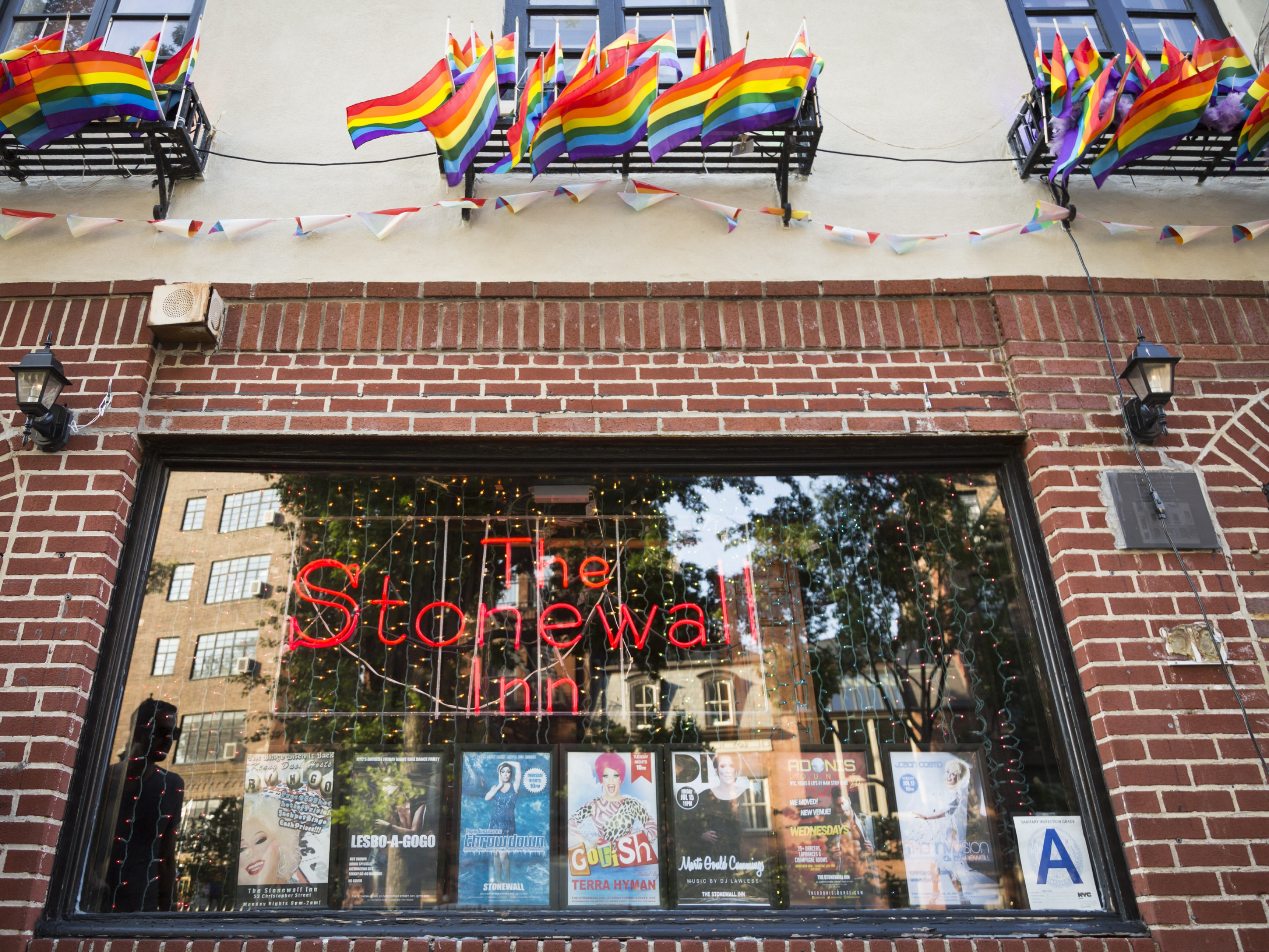 """Neone sign saying """"The Stonewall Inn"""" in a window of a brick building with many small rainbow flags flying above the window."""