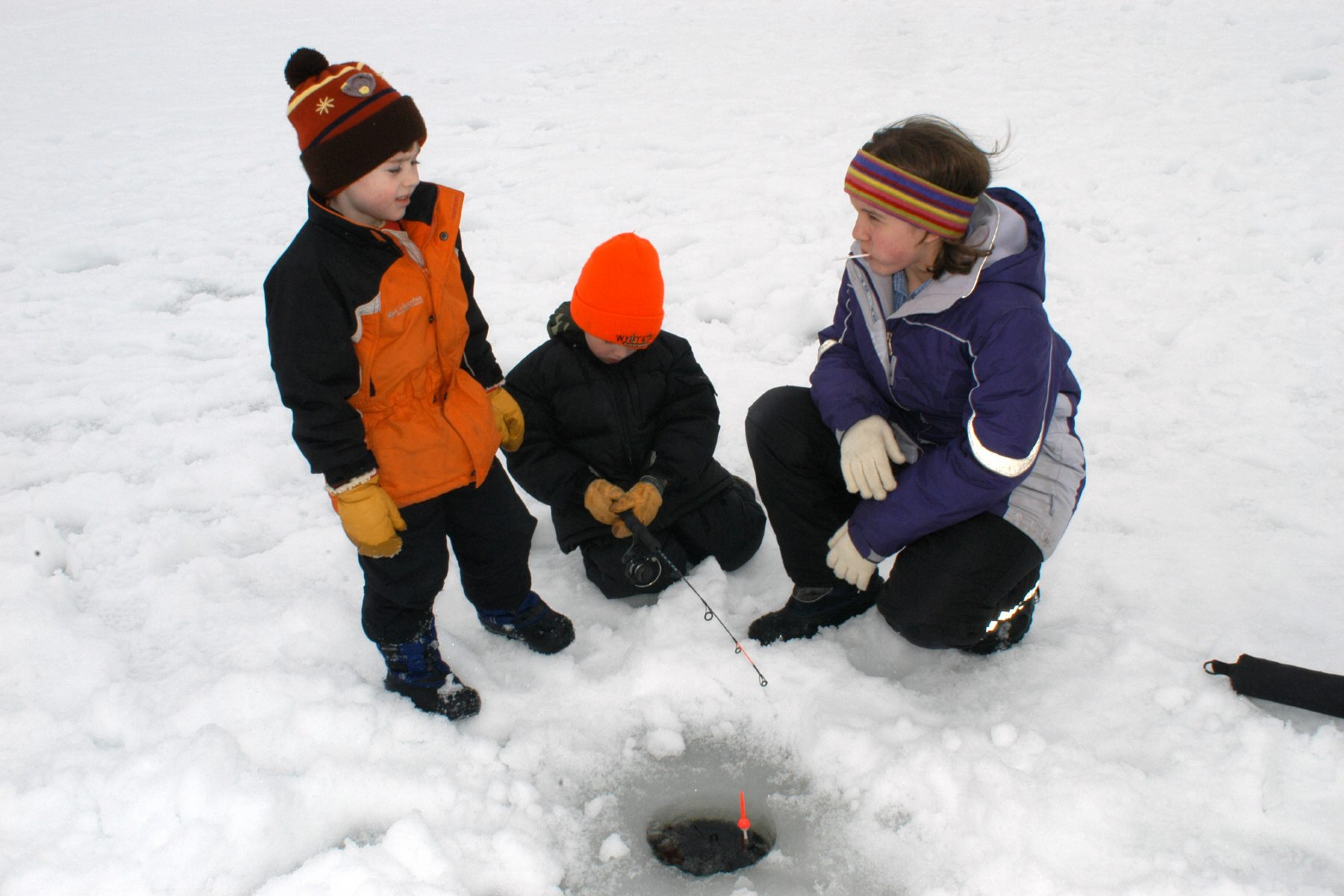 3 children on a snow-covered ice with a fishing rod through a small hole in the ice at Voyageurs National Park