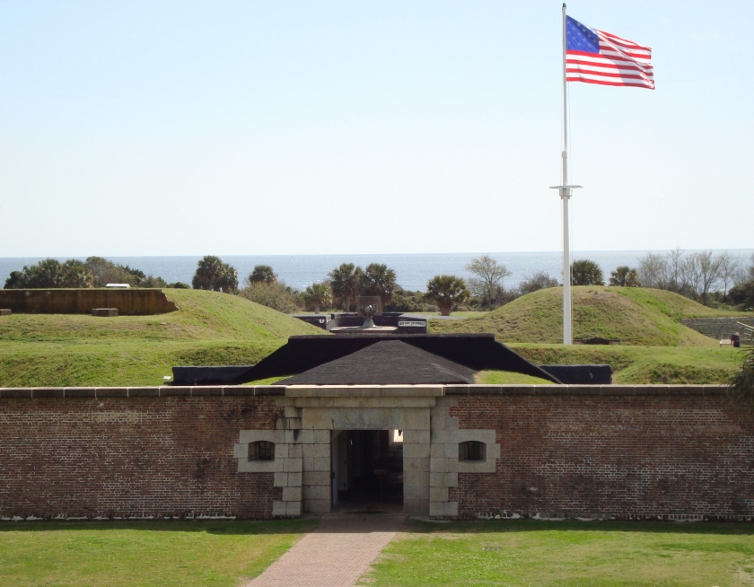 Brick fort entrance to Fort Moultrie with a flag waving at the entrance