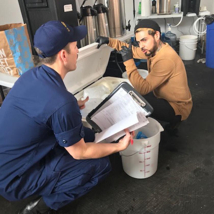 El teniente comandante Matt Kozler hablando con un vendedor de alimentos antes de la pandemia de COVID-19
