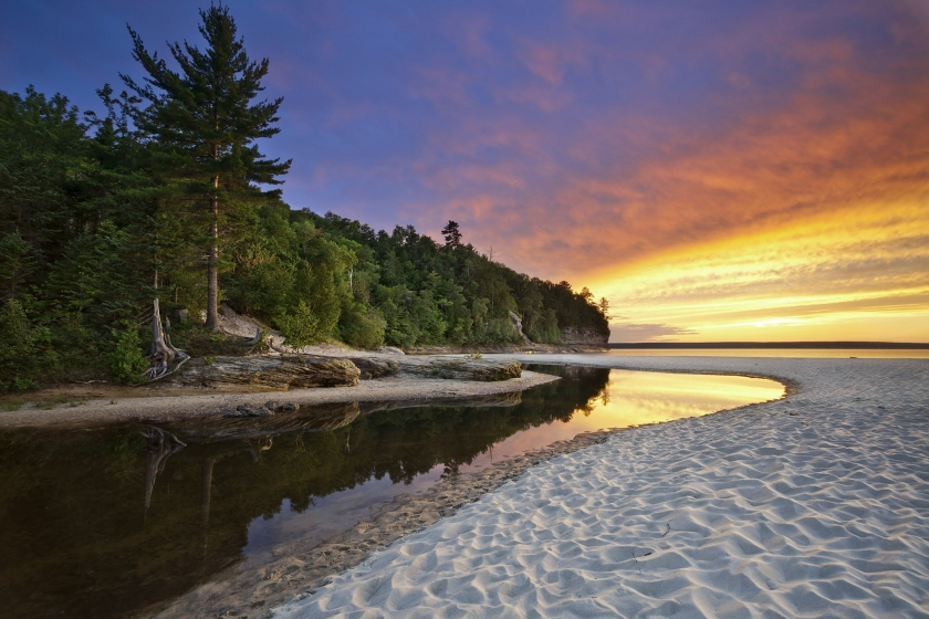 Rugged forest coastline of Pictured Rocks National Park with offset sandbar and sunset reflecting on lake