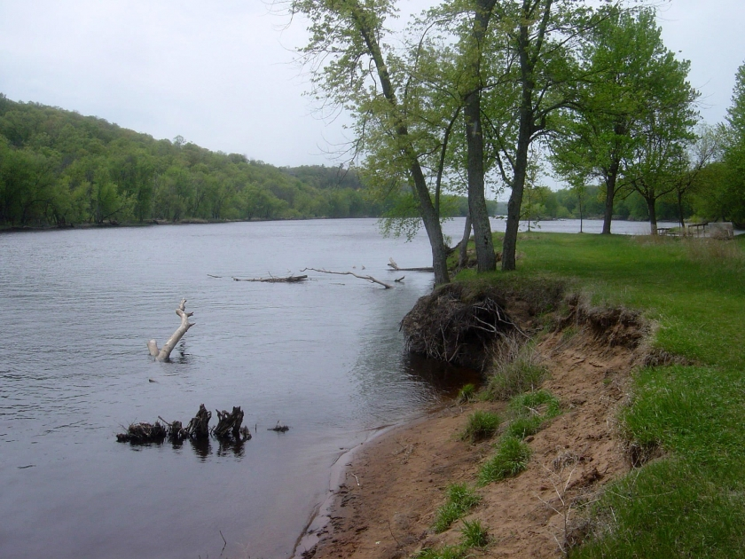 Saint Croix river flows alongside grass and trees