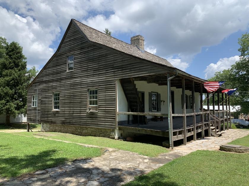 Casa de estructura de madera con techo triangular y banderas de Estados Unidos y Francia al frente